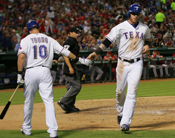 Michael Young congratulates Josh Hamilton after he scores against the Angels on Sept. 28..
