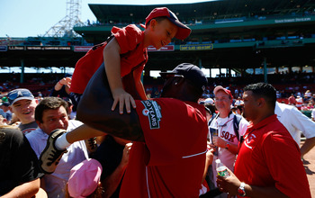 BOSTON, MA - AUGUST 26: A young fan is picked up and held by David Ortiz #34 of the Boston Red Sox during fan festivities prior to the game against the Kansas City Royals on August 26, 2012 at Fenway Park in Boston, Massachusetts.  (Photo by Jared Wickerh