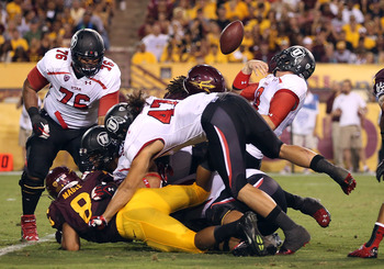 Utah and Arizona State players pile up as the ball is released in their matchup Sept. 22.