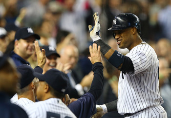 Robinson Cano receives a warm greeting from his teammates in the dugout following a home run against the Boston Red Sox