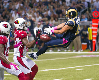 Danny Amendola (right) tries to reel in a pass against a pair of Arizona defenders.