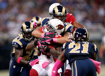 Ryan Williams (center) gets sandwiched between three Rams.