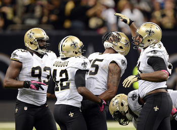 NEW ORLEANS, LA - OCTOBER 07:  Barrett Ruud #55 of the New Orleans Saints celebrates his fumble recovery with teammates Isa Abdul-Quddus #42, Junior Galette #93 and Cameron Jordan #94 preserving a 31-24 win over the San Diego Chargers at Mercedes-Benz Sup