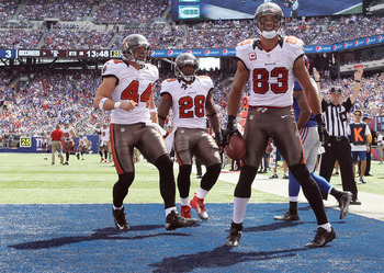 EAST RUTHERFORD, NJ - SEPTEMBER 16:  Vincent Jackson #83 of the Tampa Bay Buccaneers is congratulated by teammates Dallas Clark #44 and  D.J. Ware #28 on September 16, 2012 at MetLife Stadium in East Rutherford, New Jersey.  (Photo by Elsa/Getty Images)