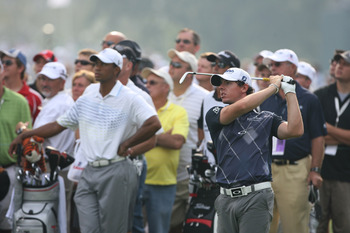 Tiger Woods off to the side as Rory McIlroy takes center stage.