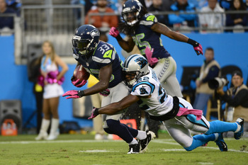 Oct 7, 2012; Charlotte, NC, USA; Seattle Seahawks running back Leon Washington (33) with the ball as Carolina Panthers defensive back Josh Thomas (22) defends in the fourth quarter. The Seahawks defeated the Panthers 16-12 at Bank of America Stadium.  Man