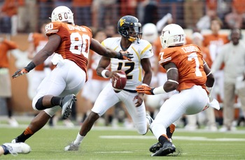Oct 6, 2012; Austin, TX, USA; West Virginia Mountaineers quarterback Geno Smith (12) avoids the rush of Texas Longhorns defensive end Alex Okafor (80) and linebacker Demarco Cobbs (7) during the first quarter at Darrell K Royal-Texas Memorial Stadium. Man