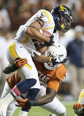 AUSTIN, TX - OCTOBER 06:  Andrew Buie #13 of the West Virginia Mountaineers is tackled by Steve Edmond #33 of the Texas Longhorns at Darrell K Royal-Texas Memorial Stadium on October 6, 2012 in Austin, Texas.  (Photo by Ronald Martinez/Getty Images)