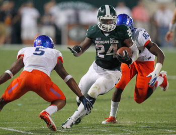 EAST LANSING, MI - AUGUST 31: Le'Veon Bell #24 of the Michigan State Spartans looks for running room between Jamar Taylor #5 and Samuel Ukwuachu #82 of the Boise State Broncos at Spartan Stadium on August, 2010 in East Lansing, Michigan. Michigan State wo