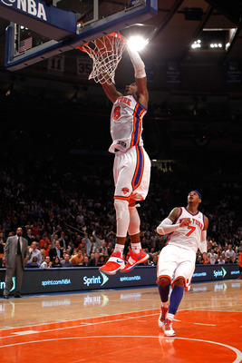 New York Knicks' JR Smith throws down a dunk in front of teammate Carmelo Anthony.
