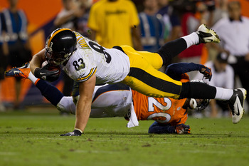 DENVER, CO - SEPTEMBER 9:  Tight end Heath Miller #83 of the Pittsburgh Steelers gets tackled by safety Mike Adams #20 of the Denver Broncos after making a catch during the third quarter at Sports Authority Field Field at Mile High on September 9, 2012 in