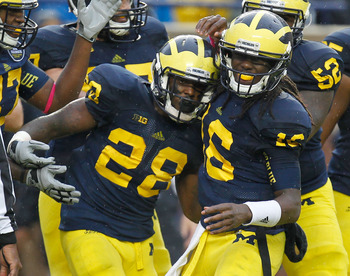 ANN ARBOR, MI - OCTOBER 13:  Fitzgerald Toussaint #28 of the Michigan Wolverines celebrates a third quarter touchdown with Denard Robinson #16 while playing the Illinois Fighting Illini at Michigan Stadium on October 13, 2012 in Ann Arbor, Michigan.  Mich