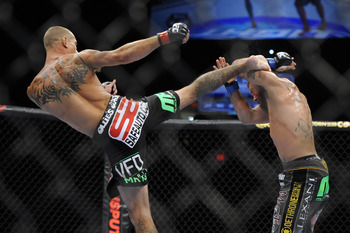 May 15, 2012; Fairfax, VA, USA; Donald Cerrone (left) lands a high kick to the blocking arms of Jeremy Stephens (right) during the Korean zombie vs Poirier event at Patriot Center.  Mandatory Credit: Rafael Suanes-US PRESSWIRE