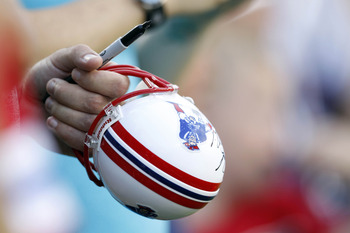Aug 9, 2012; Foxboro, Massachusetts, USA; A New England Patriots fan holds a small helmet to be autographed before the game against the New Orleans Saints at Gillette Stadium.  Mandatory Credit: Greg M. Cooper-US PRESSWIRE