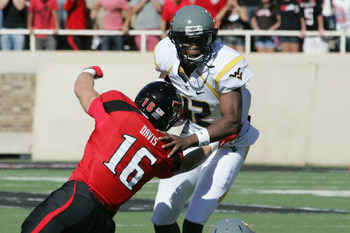 Oct 13, 2012; Lubbock, TX, USA; West Virginia Mountaineers quarterback Geno Smith (12) is pressured by Texas Tech Red Raiders safety Cody Davis (16) in the first half at Jones AT&amp;T Stadium. Mandatory Credit: Michael C. Johnson-US PRESSWIRE