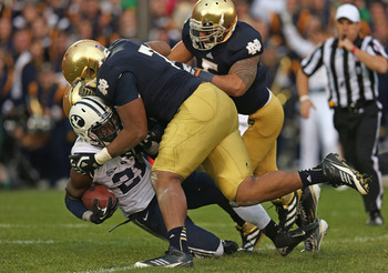 SOUTH BEND, IN - OCTOBER 20: Jamaal Williams #21 of the BYU Cougars is dropped by Stephon Tuitt #7, Louis Nix III #9 and Manti T'eo #5 of the Notre Dame Fighting Irish at Notre Dame Stadium on October 20, 2012 in South Bend, Indiana. Notre Dame defeated B