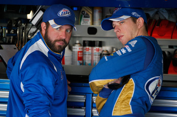 KANSAS CITY, KS - OCTOBER 20:  Brad Keselowski (R), driver of the #2 Miller Lite Dodge, talks with a crew member in the garage before the start of practice for the NASCAR Sprint Cup Series Hollywood Casino 400 at Kansas Speedway on October 20, 2012 in Kan