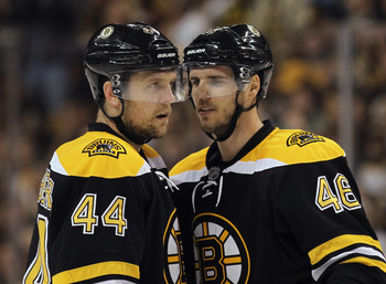David Krejci (right) speaks with teammate Dennis Seidenberg (left).