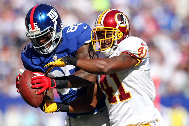 October 21, 2012; East Rutherford, NJ, USA; New York Giants tight end Martellus Bennett (85) catches a pass with pressure by Washington Redskins safety Madieu Williams (41) during the first quarter of an NFL game at MetLife Stadium. Mandatory Credit: Brad