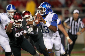 Oct 13, 2012; Fayetteville, AR, USA; Kentucky Wildcats quarterback Jalen Whitlow (13) rushes out of the pocket as Arkansas Razorbacks defensive end Trey Flowers (86) pressures at Donald W. Reynolds Razorback Stadium. Mandatory Credit: Nelson Chenault-US P