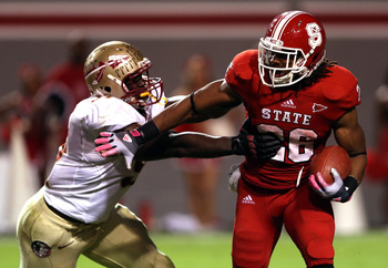 RALEIGH, NC - OCTOBER 06:  Cornellius Carradine #91 of the Florida State Seminoles tackles Tony Creecy #26 of the North Carolina State Wolfpack during their game at Carter-Finley Stadium on October 6, 2012 in Raleigh, North Carolina.  (Photo by Streeter L