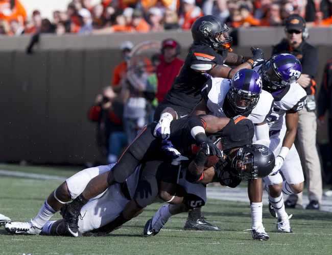 Oct 27, 2012; Stillwater OK, USA; Oklahoma State Cowboys running back Joseph Randle (1) is tackled by TCU Horned Frogs linebacker Marcus Mallet (54) and TCU Horned Frogs safety Chris Hackett (1) during the third quarter at Boone Pickens Stadium.  Mandator