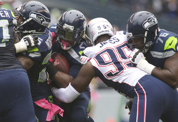SEATTLE, WA - OCTOBER 14: Marshawn Lynch #24, second from left, of the Seattle Seahawks rushes the ball against Chandler Jones #95 of the New England Patriots while Russell Okung #76 blocks during a game at CenturyLink Field on October 14, 2012 in Seattle