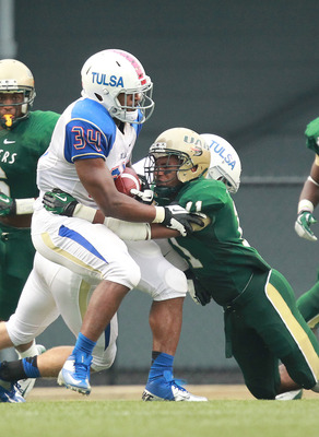 Sept 29, 2012; Birmingham, AL, USA;  UAB Blazers quarterback Austin Brown (11) wraps up Tulsa Golden Hurricanes running back Willie Carter (34) at Legion Field.   Mandatory Credit: Marvin Gentry-US PRESSWIRE