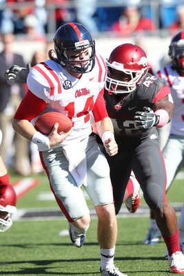 Oct 27, 2012; Little Rock, AR, USA; Ole Miss Rebels quarterback Bo Wallace (14) rushes as Arkansas Razorbacks defensive end Chris Smith (42) pursues at War Memorial Stadium. Mississippi defeated Arkansas 30-27. Mandatory Credit: Nelson Chenault-US PRESSWI