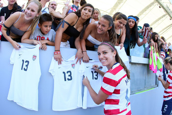 CARSON, CA - SEPTEMBER 16:  Alex Morgan #13 of the USA signs autographs for fans after their international friendly match against Australia at The Home Depot Center on September 16, 2012 in Carson, California. The USA defeated Australia 2-1.  (Photo by Vi