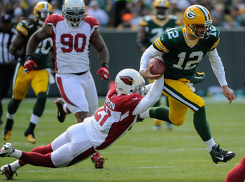 Rodgers (right) eludes Arizona's Patrick Peterson.