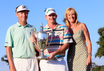 Tommy Gainey holds the McGladrey winners trophy flanked by Davis Love III and Gainey's wife, Erin.
