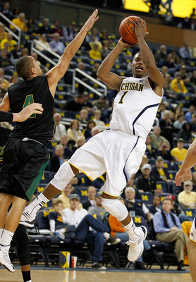 ANN ARBOR, MI - NOVEMBER 01: Glenn Robinson III #1 of the Michigan Wolverines tries to get a shot off around Quinten Calloway #4 of the Northern Michigan Wildcats during a exhibition game at Crisler Center on November 1, 2012 in Ann Arbor, Michigan. (Phot