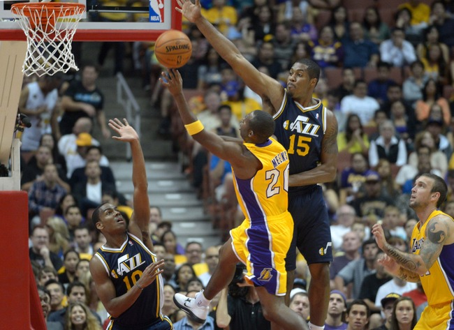 Oct 16, 2012; Anaheim, CA, USA; Los Angeles Lakers guard Jodie Meeks (20) is defended by Utah Jazz guard Raja Bell (10) and forward Derrick Favors (15) as Lakers forward Reeves Nelson (91) watches at the Honda Center. Mandatory Credit: Kirby Lee/Image of