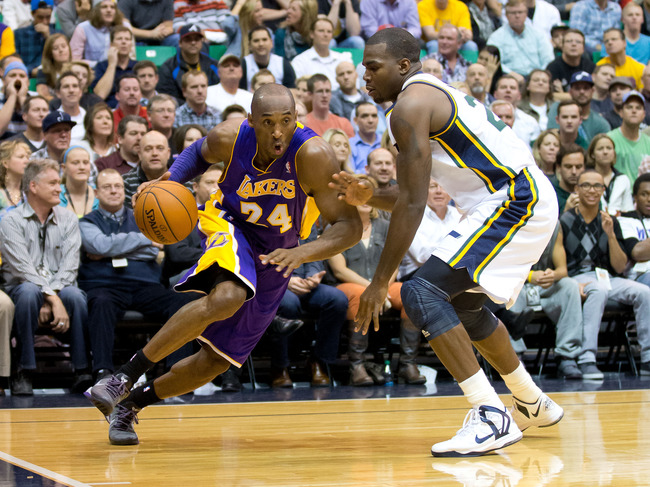 November 7, 2012; Salt Lake City, UT, USA; Los Angeles Lakers shooting guard Kobe Bryant (24) dribbles toward the basket while defended by Utah Jazz power forward Paul Millsap (24) during the first half at EnergySolutions Arena. Mandatory Credit: Russ Isa