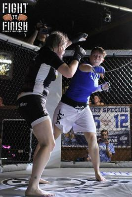 Amanda Rose (left) avoids a punch from Brooke Tibbets. (Photo credit: Sandy Hackenmueller of Fight to Finish Photography)