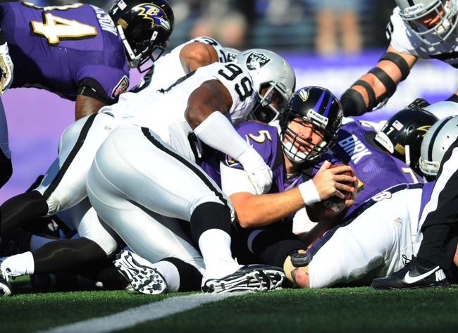 Nov 11, 2012; Baltimore, MD, USA; Baltimore Ravens quarterback Joe Flacco (5) scores a touchown as Oakland Raiders defensive end Lamarr Houston (99) defends in the first quarter at M&T Bank Stadium.  Mandatory Credit: James Lang-US PRESSWIRE
