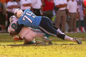 MIAMI GARDENS, FL - NOVEMBER 11:  Matt Moore #8 of the Miami Dolphins is sacked by Jarius Wynn #79 of the Tennessee Titans during a game  at Sun Life Stadium on November 11, 2012 in Miami Gardens, Florida.  (Photo by Mike Ehrmann/Getty Images)