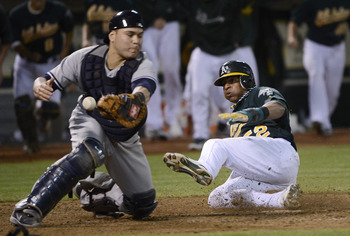 Yoenis Cespedes slides into home ahead of catcher Russell Martin's tag.