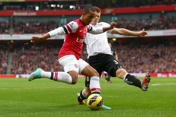 LONDON, ENGLAND - NOVEMBER 10:  Theo Walcott of Arsenal is challenged by John Arne Riise of Fulham during the Barclays Premier League match between Arsenal and Fulham at Emirates Stadium on November 10, 2012 in London, England.  (Photo by Clive Rose/Getty