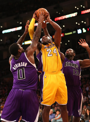 LOS ANGELES, CA - OCTOBER 21:  Kobe Bryant #24 of the Los Angeles Lakers shoots over Thomas Robinson #0 and Tyreke Evans #13 of the Sacramento Kings at Staples Center on October 21, 2012 in Los Angeles, California.   NOTE TO USER: User expressly acknowled