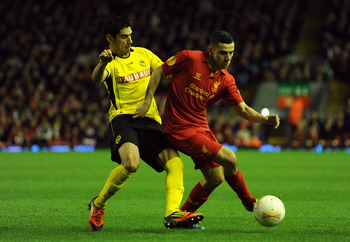 LIVERPOOL, ENGLAND - NOVEMBER 22:  Gonzalo Zarate of Young Boys competes with Oussama Assaidi of Liverpool during the UEFA Europa League Group A match between Liverpool FC and BSC Young Boys at Anfield on November 22, 2012 in Liverpool, England.  (Photo b