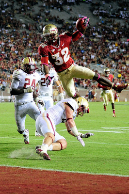 TALLAHASSEE, FL - OCTOBER 13:  James Wilder Jr. #32 of the Florida State Seminoles leaps over Sean Sylvia #19 of the Boston College Eagles for a touchdown during a game at Doak Campbell Stadium on October 13, 2012 in Tallahassee, Florida.  (Photo by Stacy