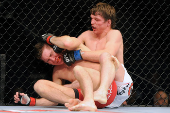 Nov 17, 2012; Montreal, QC, Canada;  Darren Elkins (white) punches Steven Siler (red) during second round action of their Featherweight bout at UFC 154 at the Bell Centre.  Mandatory Credit: Eric Bolte-US PRESSWIRE
