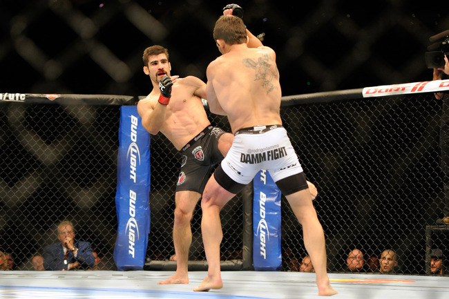 Nov 17, 2012; Montreal, QC, Canada;  Antonio Carvalho (black) kicks Rodrigo Damm (white) during second round action of their Featherweight bout at UFC 154 at the Bell Centre.  Mandatory Credit: Eric Bolte-US PRESSWIRE