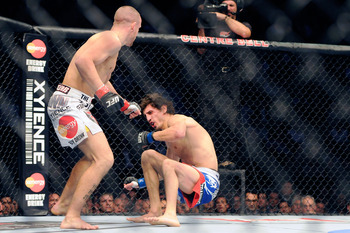 Nov 17, 2012; Montreal, QC, Canada;  Mark Hominick (white) sends Pablo Garza (blue) to the mat during first round action of their Featherweight bout at UFC 154 at the Bell Centre.  Mandatory Credit: Eric Bolte-US PRESSWIRE