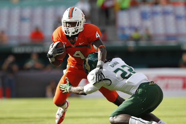 MIAMI GARDENS, FL - NOVEMBER 17: Phillip Dorsett #4 of the Miami Hurricanes runs with the ball and is tackled by George Baker #22 of the South Florida Bulls on November 17, 2012 at Sun Life Stadium in Miami Gardens, Florida. (Photo by Joel Auerbach/Getty
