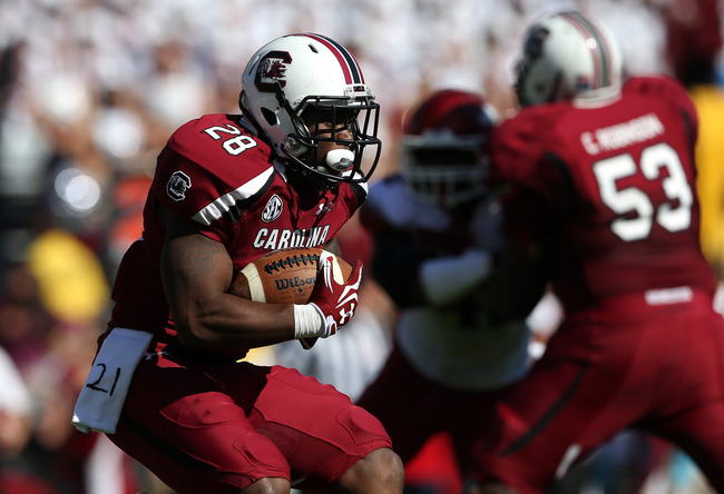 COLUMBIA, SC - NOVEMBER 10:  Mike Davis #28 of the South Carolina Gamecocks runs with the ball as a towel hangs from his side supporting his teammate Marcus Lattimore #21 who was injured in a recent game during their game against the Arkansas Razorbacks a