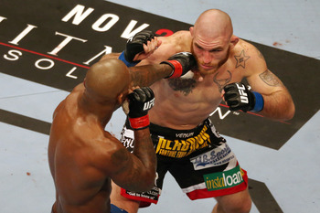 Nov 17, 2012; Montreal, QC, Canada; Tom Lawlor (right) takes a punch from Francis Carmont during their Middleweight bout at UFC 154 at the Bell Centre. Mandatory Credit: Tom Szczerbowski-US PRESSWIRE