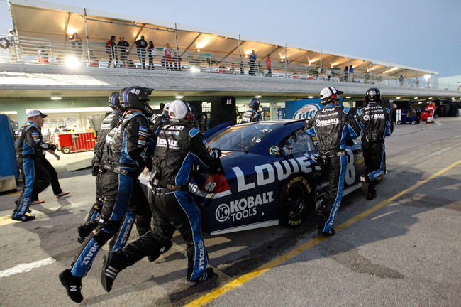 HOMESTEAD, FL - NOVEMBER 18:  Crew members push the #48 Lowe's Chevrolet, driven by Jimmie Johnson, through the garage area after an incident in the NASCAR Sprint Cup Series Ford EcoBoost 400 at Homestead-Miami Speedway on November 18, 2012 in Homestead,